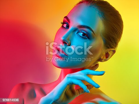 926617828istockphoto High Fashion model woman in colorful bright lights posing in studio 926614536