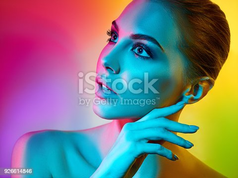 926617828istockphoto High Fashion model woman in colorful bright lights posing in studio 926614846