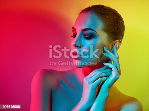 926617828istockphoto High Fashion model woman in colorful bright lights posing in studio 926616968