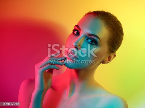 926617828istockphoto High Fashion model woman in colorful bright lights posing in studio 926617216