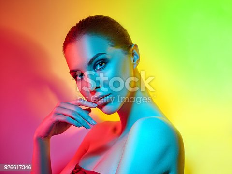 926617828istockphoto High Fashion model woman in colorful bright lights posing in studio 926617346