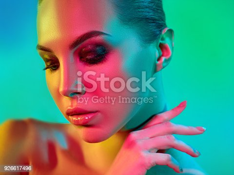 926617828istockphoto High Fashion model woman in colorful bright lights posing in studio 926617496