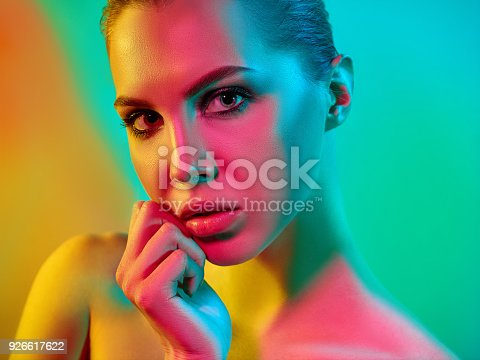 926617828istockphoto High Fashion model woman in colorful bright lights posing in studio 926617622