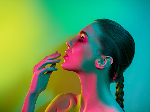 istock High Fashion model woman in colorful bright lights posing in studio 926617828
