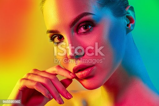 926617828istockphoto High Fashion model woman in colorful bright lights posing in studio 945595560