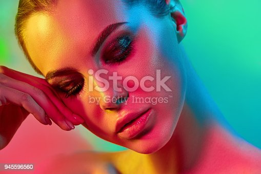 926617828istockphoto High Fashion model woman in colorful bright lights posing in studio 945596560