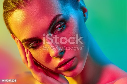 926617828istockphoto High Fashion model woman in colorful bright lights posing in studio 945597208