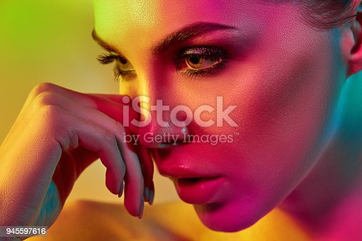 926617828istockphoto High Fashion model woman in colorful bright lights posing in studio 945597616