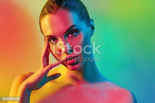 926617828istockphoto High Fashion model woman in colorful bright lights posing in studio 945598226