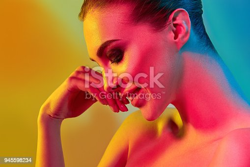926617828istockphoto High Fashion model woman in colorful bright lights posing in studio 945598234