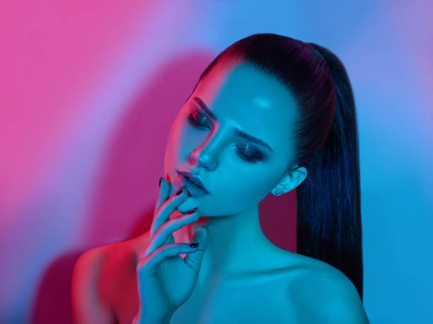 high fashion model frau im bunten lichterglanz posiert im studio - make up mode stock-fotos und bilder