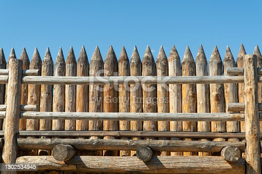 high fence made of wooden logs pointed at the top. old picket stockade