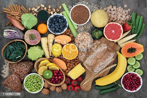 High fibre super food with whole grain bread loaf and rolls, fruit, vegetables, whole wheat pasta, cereals, seeds and nuts. Foods omega 3, anthocyanins, antioxidants and vitamins. Top view.