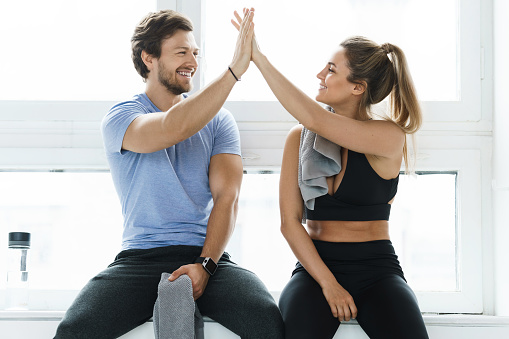 High five between man and woman in the gym after fitness workout. Personal trainer and his client achieving results during a training.