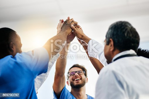 Shot of a diverse team of doctors giving each other a high five in a hospital