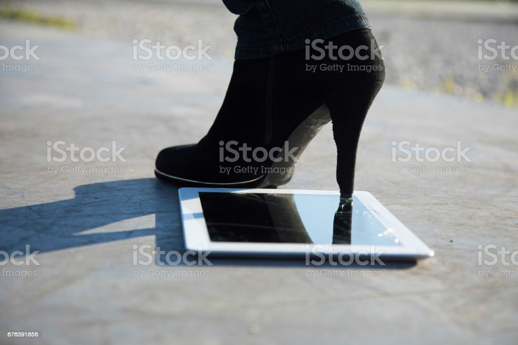 High heel boot steps on tablet breaking the glass screen stock photo