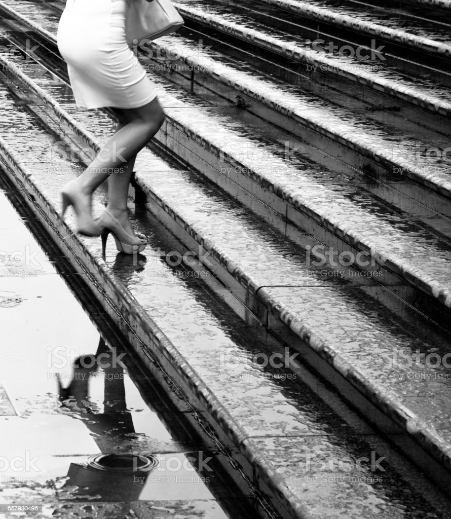 High heels climbing up the wet stairs stock photo