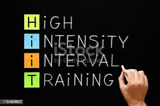 Hand writing fitness workout acronym HIIT - High Intensity Interval Training with white chalk on blackboard.