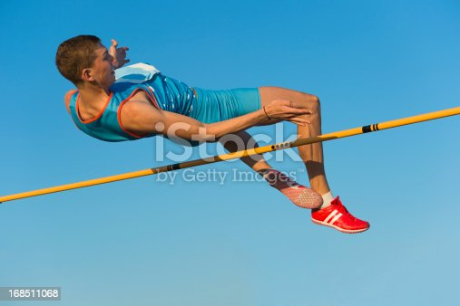 Side view of young athlete jumping over the lath