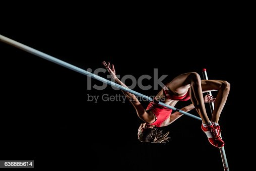 Young female high jumper clearing bar.