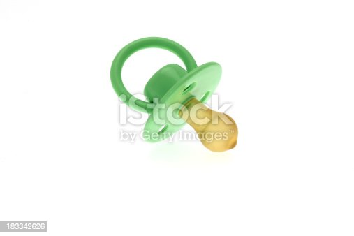 High key image of a traditional infants green dummy or pacifier taken against a white background.