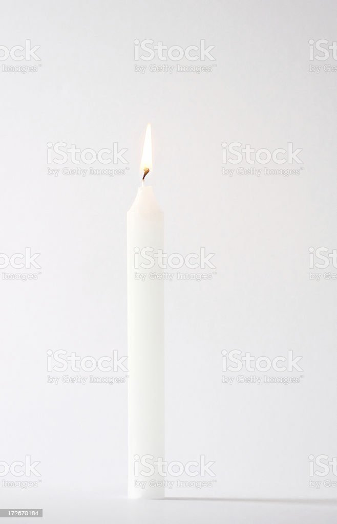 High key white lit candle stock photo