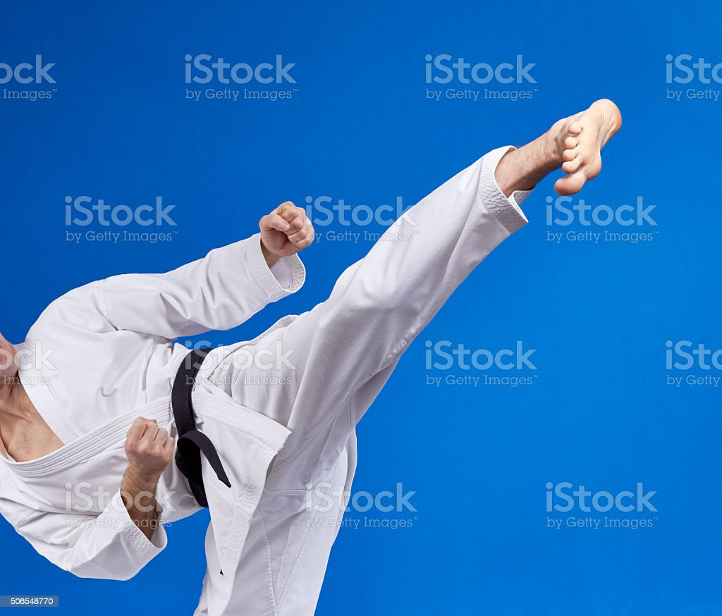 High kick athlete is beating with a black belt stock photo