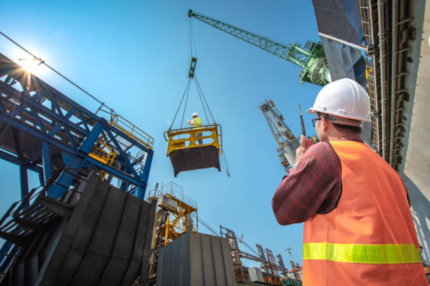 High level at risk engineering, loading master connecting to gantry crane driver by walkie talkie for lifting safety in loading the goods or shipment, lifting by gantry crane, working at risk on the high level insurance hooikoorts stock pictures, royalty-free photos & images