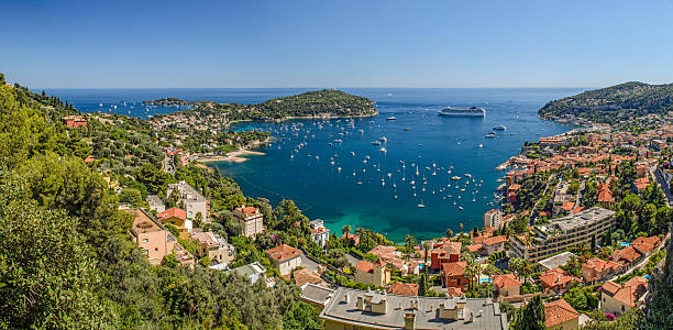 High Level Panorama of Viilefranche Cote d'Azur Ultra wide angle high level panorama of Villefranche bay, Nice, Cote d'Azur, France, showing Mont Boron to the West and Cap Ferat to the East, with the clear  turquoise meditaerannean sea in the bay under a clear blue sky mediterranean sea stock pictures, royalty-free photos & images