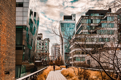 New York, USA - February 11, 2020: Modern glass buildings and walkway along the High Line public park in Chelsea, Manhattan, United States. Touristic place.