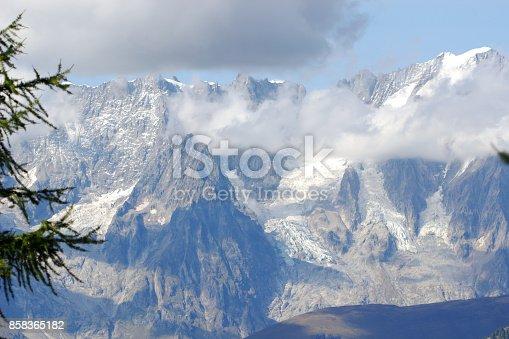 High mountain landscape with dark rain clouds, foggy blurred background.