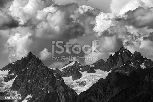 High mountains with glacier and cloudy sky at summer day. Caucasus Mountains, Georgia, region Svaneti. Black and white toned landscape.