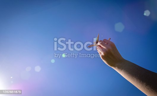 istock High plane white toy in kid hand fly in sun light sky. Airplane flight, aircraft travel in bright sunlight background. Air concept. 1252651875