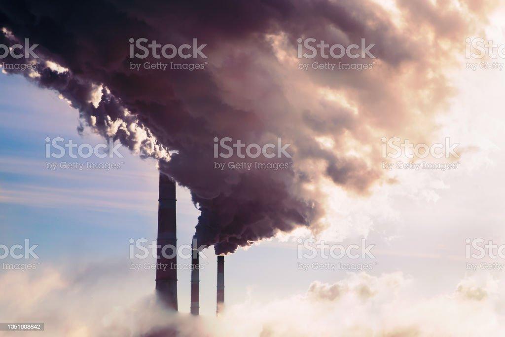 Hoog risico op verontreiniging van kolencentrale. Schoorsteen van roken. foto