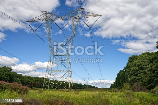 Tall towers carry high tension wires moving electricity cross-country through rural areas while feeding the power distribution network. Pennsylvania, USA.