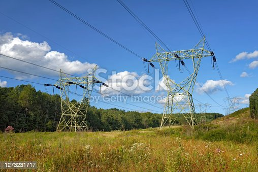 Electric high power lines across a wooded landscape, part of the energy grid in the northeastern USA in Pennsylvania.