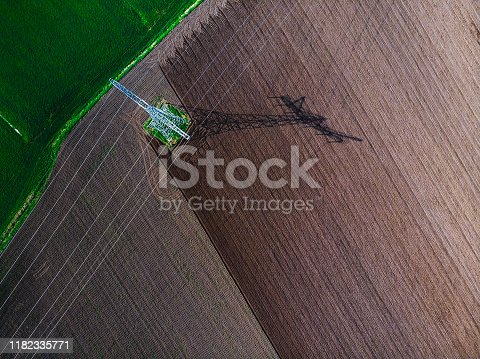 Drone shot of powerlines over agriculture fields during a day in summer