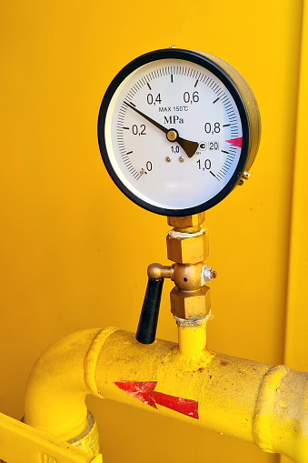 High pressure gauge meter or manometer installed to yellow gas tube in yellow cabinet