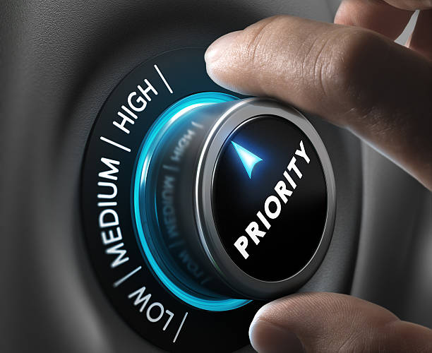 High Priority Man fingers setting priority button on highest position. Concept image for illustration of priorities management. beat the clock stock pictures, royalty-free photos & images