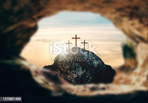 istock High resolution. Easter Sunday concept: Empty tomb stone with cross on meadow sunrise background. 3d rendering 1223801483