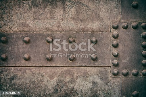 Part of a weathered metal door with rivets.