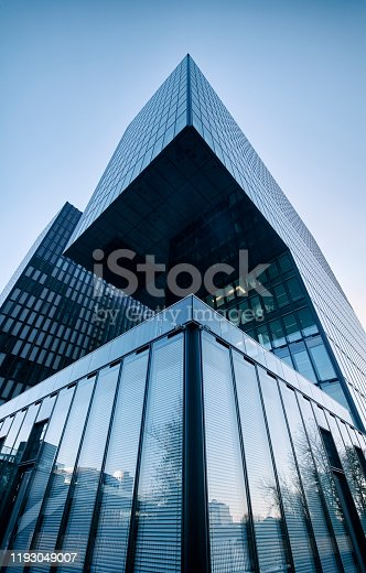 Low angle view of a modern office building at Media Harbor Düsseldorf, steel and glass business background.