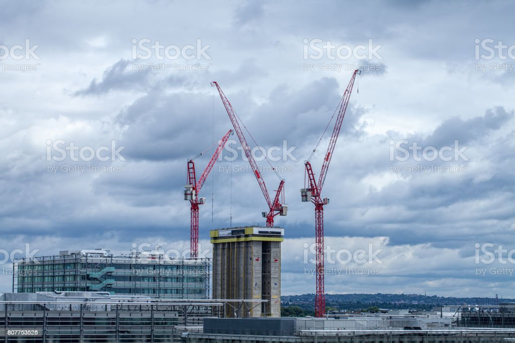 High rise building construction with red cranes over London. stock photo