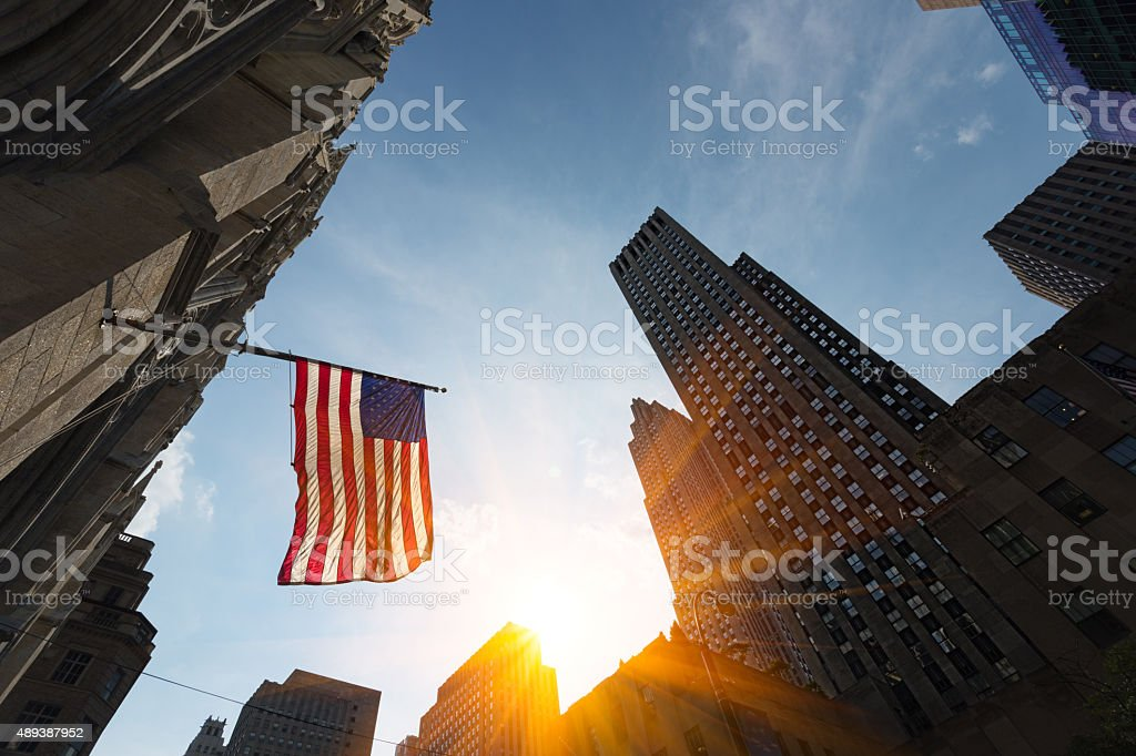 High rise buildings and US Flag at sunset stock photo