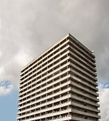 High rise residential concrete building in concrete brutalism style with heavy overcast white and gray clouds.