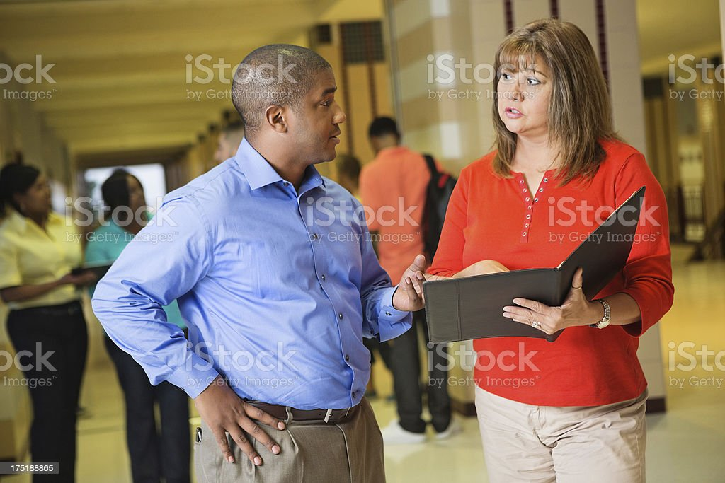 High school administrators discussing something after class stock photo