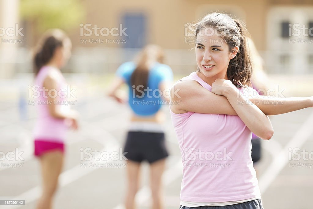 High school athlete stretching limbs before track meet race stock photo