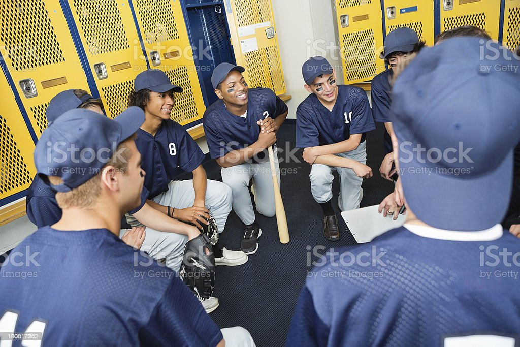 High school baseball team huddled in locker room with coach stock photo