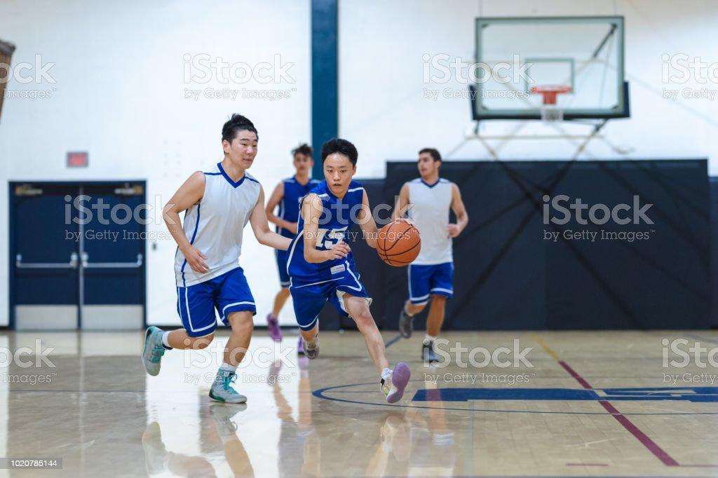 A high school player dribbles and tries to get around his opponent,...