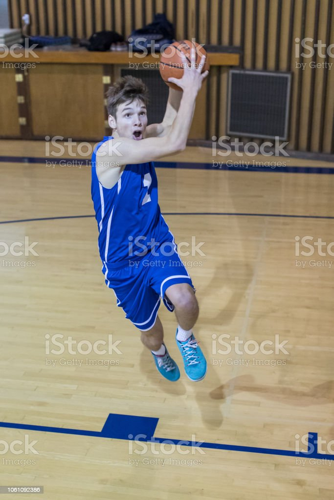 A high school basketball player takes a giant step before leaping...